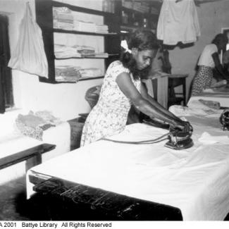 A black and white photograph of a group of people at Beagle Bay doing laundry. There is a young person ironing a large sheet.