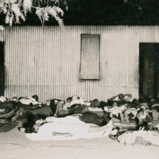 A black and white photograph of a large group of people at The Bungalow. They are sleeping on the ground outside a building. They are lying on blankets, and three or four people share one blanket.