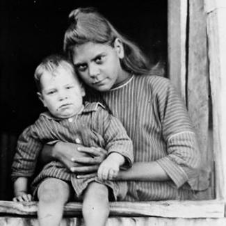 A black and white photograph of a child and adult at The Bungalow. The adult is standing near a window and is holding a toddler who is sitting on the window-sill.
