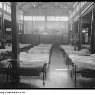 A black and white photograph of the dormitory at Castledare. A large number of metal framed beds occupy the room, and lying on top of each bed is an identical striped quilt. A statue of Mary and Jesus overlooks the beds.