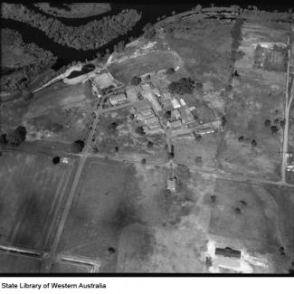 A black and white photograph of Castledare taken from an aeroplane. Beside Castledare are the sinuous rills of the Canning River, and much of the riverfront has been cleared for agricultural purposes.