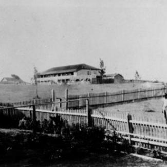 A black and white photograph of Cherbourg Dormitory. There is a long picket fence crossing across the property.