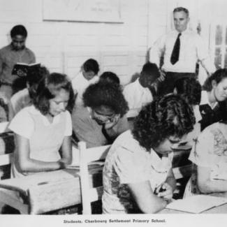 A black and white photograph of a class of young students at Cherbourg Dormitory. They are reading. There is an older adult standing in the back.