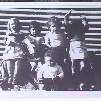 A black and white photograph of a small group of young children from Colebrook Home. They are sitting beside a corrugated iron sheet and are singing.