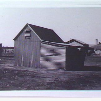 A black and white photograph of a small building at Colebrook Home. The building is constructed out of corrugated iron sheet metal, with a small vent near the roof.