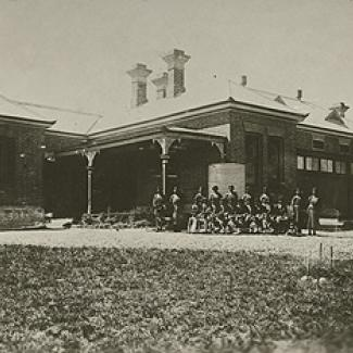 A black and white photograph of Cootamundra Girls Home. A group of residents and staff members are assembled in front of the building, preparing for the photograph.