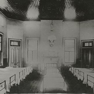 A black and white photograph of the sleeping quarters of Cootamundra Girls' Home. Beds line the left, right and centre of this room.