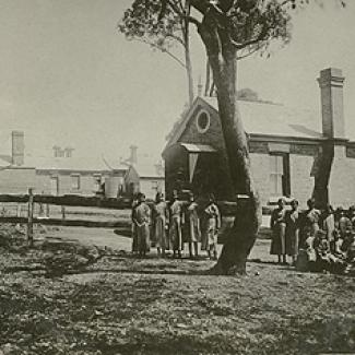 A black and white photograph of a building at Cootamundra Girls' Home. Standing in front of the building there are a group of  residents and  staff members.