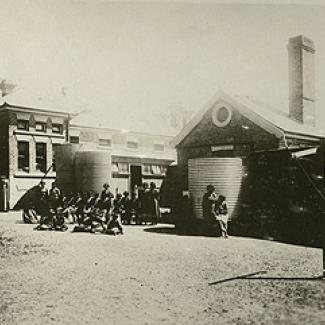 A black and white photograph of the exterior of Coota Mundra Girls' Home. A group of residents and staff members are standing beside water holding tanks.