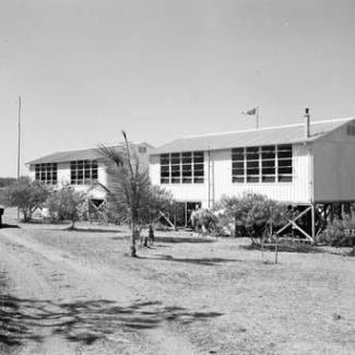 A black and white photograph of two buildings at Croker Island Mission. There is an unsealed road winding to the left of the buildings, and small trees separate the buildings from the road.