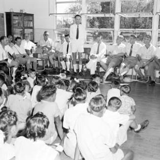 A black and white photograph of people assembled inside a building at Croker Island Mission. The adults are seated, while the children are sitting on the floor. They are all listening to one adult who is standing and speaking.