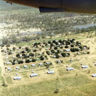 A colour photograph of Doomadgee Mission taken from an aeroplane. Buildings of various sizes, mostly small, are constructed in rows and spaced in regular intervals.