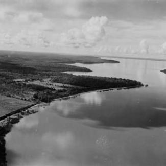 A black and white photograph of Garden Point Mission taken from an aeroplane. The shoreline of the Timor Sea is visible, along with Kings Cove as well as Harris Island.