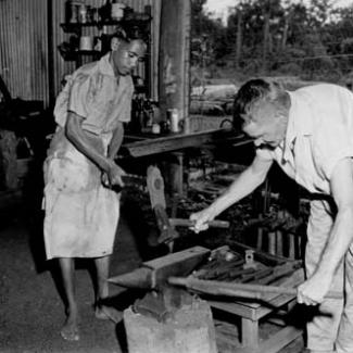 A black and white photograph of the forge at Garden Point Mission. An older child and an adult are using hammers at an anvil.