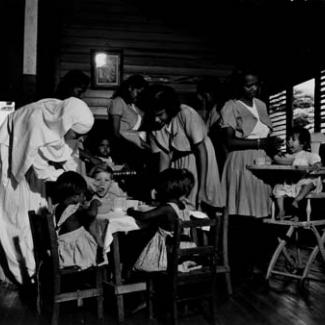 A black and white photograph of young children at Garden Point Mission. They are sitting at a table, eating and drinking, and are being assisted by several adults.