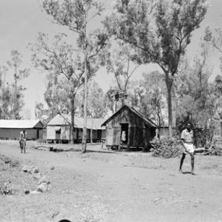 A black and white photograph of Groote Eyelandt Mission. Several small buildings are among tall trees, and a person is riding a bicycle along an unpaved track.
