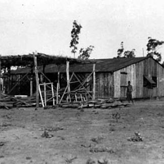 A black and white phoograph of a building at Groote Eyelandt Mission. Beside the building is a shelter roughly constructed from wooden planks, topped with branches as a makeshift roof.