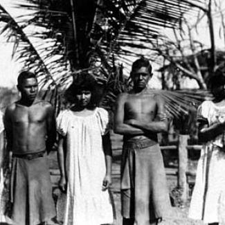 A black and white photograph of a small group of people at Groote Eyelandt Mission. They are assembled in a row, preparing for their photograph to be taken.