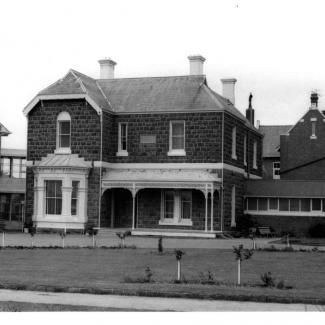 A black and white photograph of the front face of a building at St Joseph's Sebastopol. The building is constructed from stone masonry and consists of two floors. The ground floor has a porch with ornate filigree latticework.