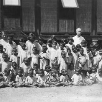 A black and white photograph of a group of children at the Kahlin Compound. The children are assembled, either sitting or standing, in preparation for a photograph. An adult is standing in the back.,