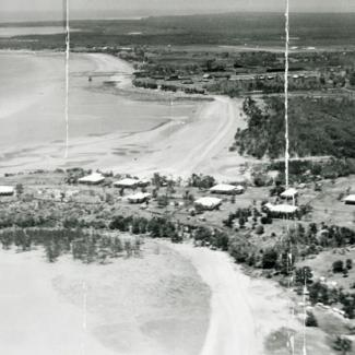 A black and white photograph of Kahlin Compound taken from an aeroplane. There are several buildings in the compound, and the shores of Cullen Bay and Mindil Beach are visible.