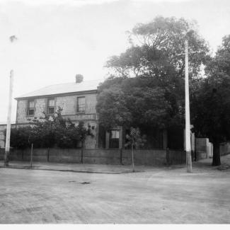 A black and white photograph of the front of Kennion House. The building has a brick face, and several trees which shield the ground floor windows from the street.