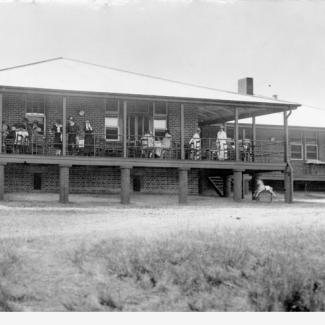 A black and white photograph of the rear porch of Kennion House. There are a large group of people on the porch, either sitting or gazing out across the grass field.