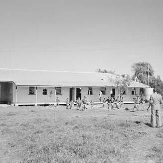 A black and white photograph of a building at Kinchela Boys' home. A group of children are running in front of the building. An adult is watching them.