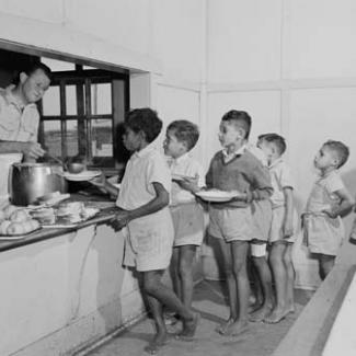 A black and white photograph of a group of children at Kinchela Boys' Home. They are are queued in the cafeteria, waiting to be served a meal by a staff member.