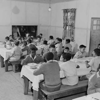 A black and white photograph of children at Kinchela Boys' Home. They are seated in the dining hall and eating a meal.