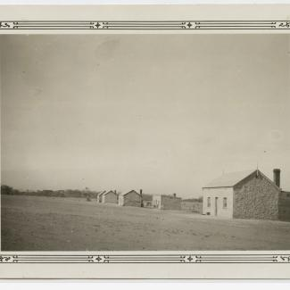 A black and white photograph of several buildings at Koonibba Lutheran Children's Home. The buildings are small, with stone-masonry and coarse plaster walls. Each building has two windows separated by a single door as well as a chimney.