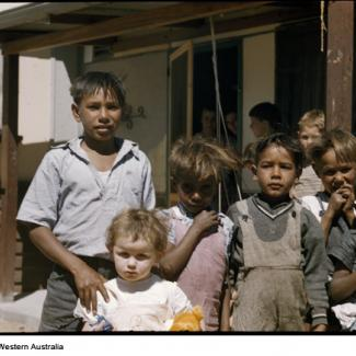 A colour photograph of several  young children at Marribank Mission. They are outside in the open, standing together in a small group.