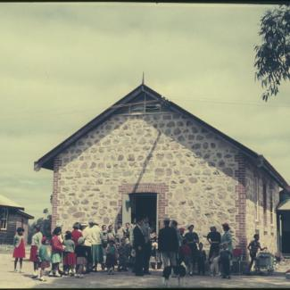 A colour photograph of a crowd at Marribank Mission. They are standing outside of a building with a stone-masonry façade.