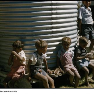 A colour photograph of a few young children at Marribank Mission. They are seated next to a water holding tank constructed from corrugated iron sheet metal.