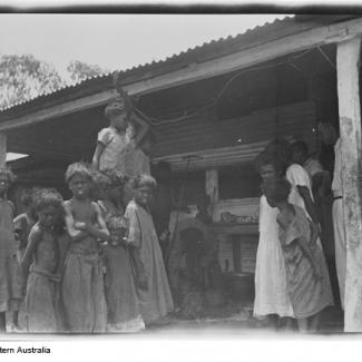 A black and white photograph of a group of people at Moore River Native Settlement. They are standing underneath a shelter made out of corrugated iron.