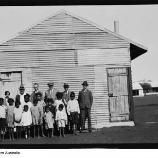 A black and white photograph of a group of people at Moore River Native Settlement. The children are all standing in front of a building which is made out of corrugated iron sheeting. The children are assembled together, with staff standing in the back row, and they are all are preparing for their photograph to be taken.