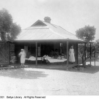 A black and white photograph of a medical ward at Moore River Native Settlement. There are a group of people lying in bed on the porch. There are staff members standing near them.