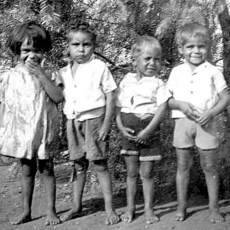 A black and white photograph of young children at Mount Margaret Mission. They are standing side-to-side in a row. The child on the left is hiding a laugh.