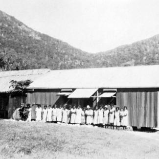 A black and white photograph people at Palm Island Dormitory. They are standing side-to-side in a row. They are outside and in front of a building constructed of corrugated iron sheet metal.