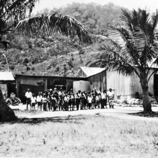 A black and white photograph of people at Palm Island Dormitory. They are standing side-to-side in front of a building constructed of corrugated iron sheet metal. There are two palm trees, one at either side of the group.
