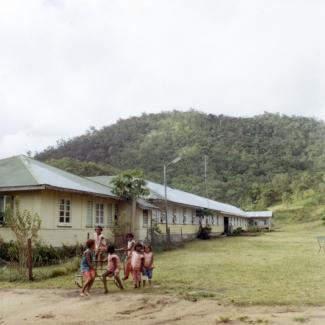 A colour photograph of a small group of children at Palm Island Dormitory. They are playing in front of the Girls' Dormitories, which are nestled at the foot of a hill that is dense with vegetation.
