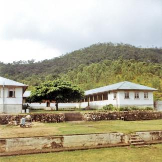 A colour photograph of the Boys' Dormitories at Palm Island Dormitory. The buildings are at the foot of a hill that is dense with vegetation, and a large tree is growing in the middle of the dormitories.