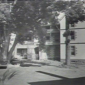 A black and white photograph of Parramatta Girls' Industrial School. There are two large trees growing in front of the building, and their foliage is shading benches beneath them.