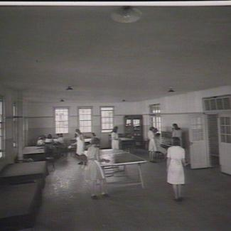 A black and white photograph of a room inside a building of Parramatta Girls' Industrial School. Inside the room are several girls, some of whom are playing table tennis, while others are at a piano.