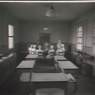 A black and white photograph of several staff members inside a room at Parramatta Girls' Industrial School. They are seated around a circular table and are listening to one person who is standing up and speaking.