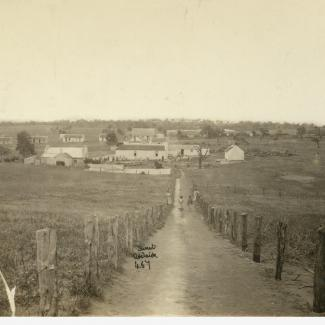 A sepia-toned photograph of Point McLeay Mission. A narrow, unpaved track is leading down to the Mission. The mission consists of several small buildings clustered together in a large, open field.