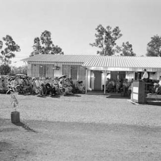 A black and white photograph of a crowd at Retta Dixon Home. They are seated outside in the open are are listening to a person speaking at a podium.