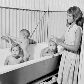 A black and white photograph of a small group of children at Retta Dixon Home. Three younger children are in a bath, while an older child is assisting them.