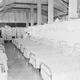 A black and white photograph of the sleeping quarters at Retta Dixon Home. Arranged in rows are a large number of metal framed beds. A single person is fitting sheets over the beds.