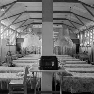 A black and white photograph of the sleeping quarters at Retta Dixon Home. Arranged in rows are a large number of metal framed beds. A single person is seated on one bed.